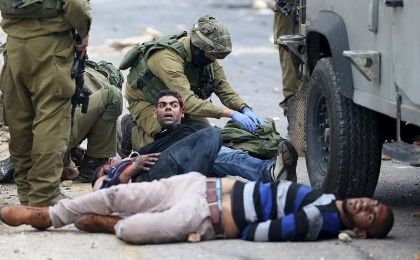 Israeli soldiers detain wounded Palestinian protesters during clashes near the Jewish settlement of Beit El.