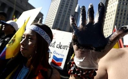 A man holds up his hand covered in oil during a protest against Chevron in New York, October 15, 2013.