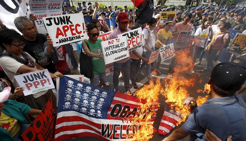 "Activists carry signs with slogans like ""No to imperialist globalization!"" while burning a mock U.S. flag during an anti-APEC protest."