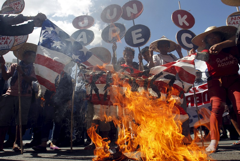 Dozens of protesters burn a mock U.S. flag in an APEC protest.