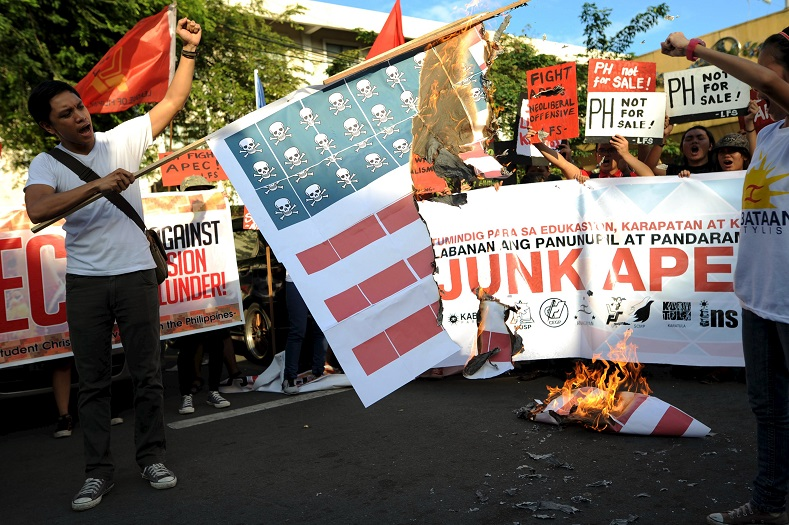 Activists burn a U.S. flag replica made of paper during an anti-APEC rally.