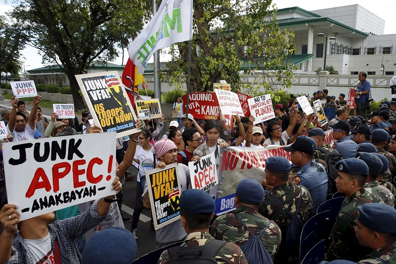"Policemen and soldiers block dozens of members of ""Bayan"" movement as they march towards the U.S. embassy in Manila."
