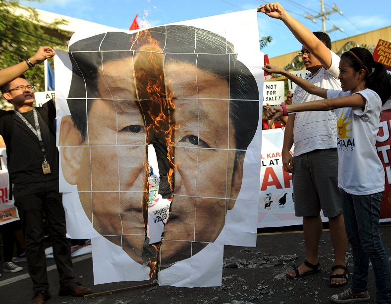 Protesters burn an image of Chinese President Xi Jinping in protest of the leader's visit to Manila for the APEC summit.