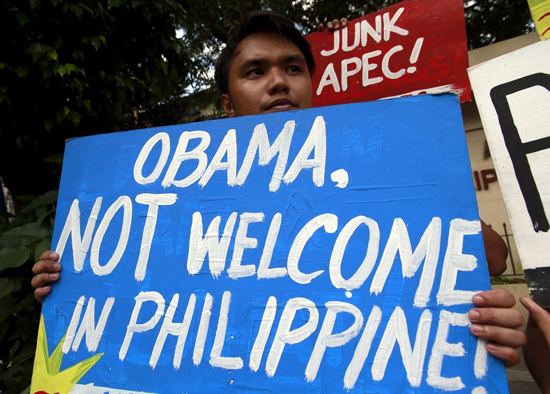 A student displays placards during a protest in front of the university in Manila on Nov. 5 in the lead-up to APEC 2015.