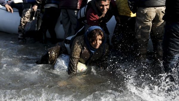 An Afghan refugee falls into the sea as refugees and migrants arrive on a raft on the Greek island of Lesbos.
