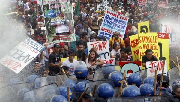 """Protesters shout as they march toward the APEC Summit in Manila on Nov. 19, 2015."""