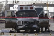 Forensic workers are seen at a crime scene where an ambulance had been attacked earlier by gunmen in Ciudad Juarez, Mexico.