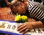Teresa Munoz mourns over the coffin of her daughter Maria Jose Alvarado during a wake for Maria Jose and her sister Sofia in Honduras Nov. 20, 2014.