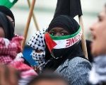 A Bedouin woman, covering her face with a Palestinian flag, marches during a protest in Israel.
