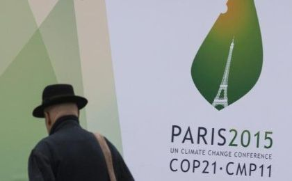 A passerby walks in front of posters for the forthcoming COP 21 World Climate Summit in Paris, France, Nov. 2, 2015.