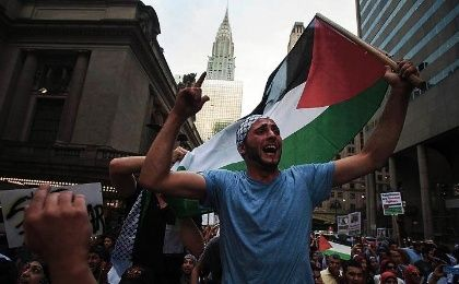 "A man waves the Palestinian national flag as he shouts, ""Free Palestine"", during a march demanding an end to the escalating Israeli-Palestinian hostilities in that region, in midtown Manhattan, New York July 9, 2014."