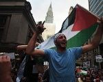 A man waves the Palestinian national flag as he shouts,