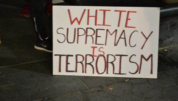 A banner condemns white supremacy as a form of terrorism.