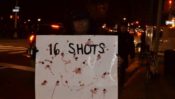 A protester holds a banner representing the 16 shots fired by police on unarmed teenager Laquan McDonald in Chicago.