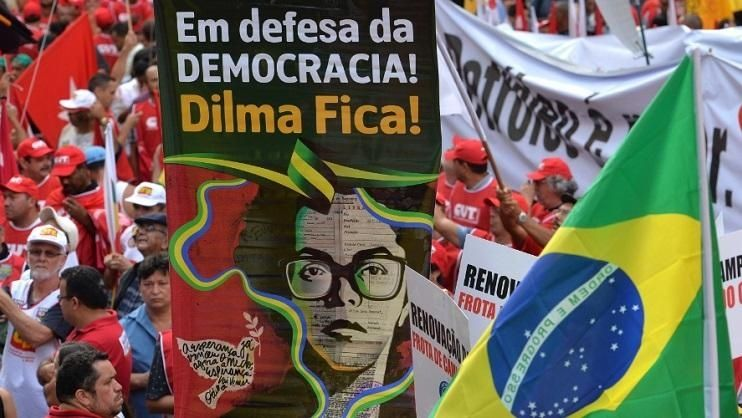 "A photo from a March 13, 2015 rally in Sao Paulo features a poster with an image of a young Dilma Rousseff that reads, ""In defense of democracy, Dilma stays!"""