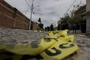 Yellow police tape lies on the road as federal agents work at a crime scene in Mexico.