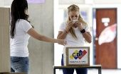 Lilian Tintori, the wife of jailed opposition leader Leopoldo Lopez, kisses the ballot before casting her vote in Caracas.