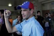Venezuelan opposition leader Henrique Capriles shows his ink-stained finger after casting his vote at a polling station during a legislative election, in Caracas.