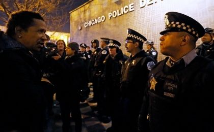 A demonstrator faces a line of police in front of the Chicago Police Department during protests in Chicago, November 24, 2015.