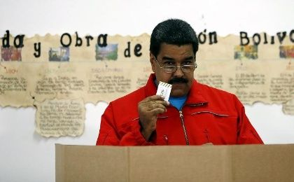 Venezuela's President Nicolas Maduro shows his ballot before casting his vote at a polling station during a legislative election, in Caracas Dec. 6, 2015.