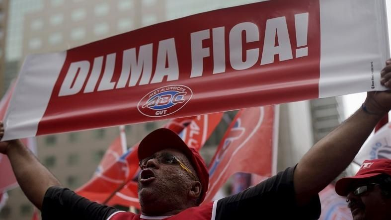 "A demonstrator holds a sign that reads ""Dilma Stays"" at a protest against the impeachment proceedings against President Dilma Rousseff, Brazil, Dec. 8, 2015."