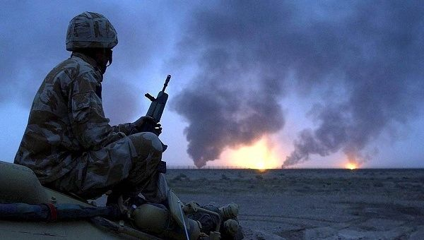 Photo shows a British soldier watching oil wells on fire in Southern Iraq in March 2003.