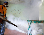 A worker from the municipality of Sucre fumigates a hospital to help control the spread of dengue fever in the Petare district of Caracas Sep. 22, 2014