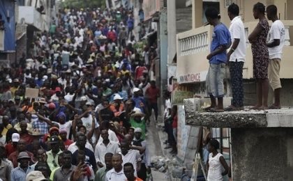Residents watch protesters marching during a demonstration against the results of the presidential elections in Port-au-Prince, Haiti.