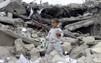 A boy collects toys in the rubble of a house destroyed by an airstrike in Yemen