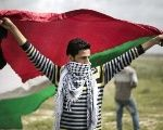 A protester waves a Palestinian flag towards the Israeli border fence between Israel and the Gaza Strip during a protest in 2014.