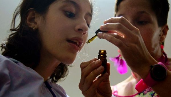 Ines Cano administers medical marijuana to her daughter Luna Valentina (L) at their home in Medellin on November 25, 2015; Valentina, 12, was born with refractory epilepsy and uses cannabis to calm her seizures.