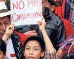 "Protesters hold a sign saying ""no more corruption"