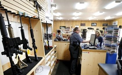 David Warren rings up customers sales next to assault rifles on display at the Ringmasters of Utah gun range and store.