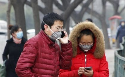 Pedestrians wearing protective masks are seen on a street on a heavily polluted day in Beijing, December 26, 2015.