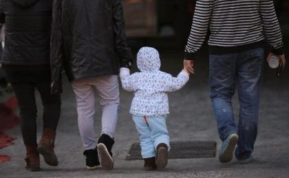 A girl holds the hands of her parents as they walk on a street in Beijing, Nov. 18, 2013