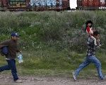 A Salvadoran father carries his son while running next to another immigrant as they try to board a train heading to the Mexican-U.S. border, in Huehuetoca, near of Mexico City, June 1, 2015.