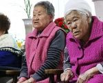 Former South Korean 'comfort women' watch a news report as they wait for the result of meeting between foreign ministers of South Korea and Japan.