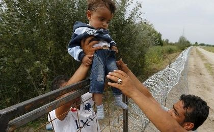 A Syrian refugee lifts a child over a fence on the Hungarian-Serbian border near Asotthalom, Hungary, Aug. 25, 2015.