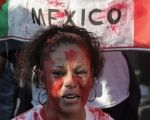 A demonstrator protests violence in Mexico in front of a bloody Mexican flag.