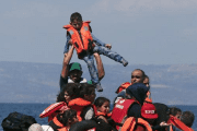 A man raises a child into the air as Syrian and Afghan refugees clamber around a deflated dinghy some 100 meters from the Greek island of Lesbos Sept. 2015.
