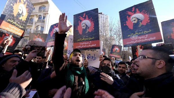 Protesters chant and hold pictures of Shiite cleric Sheikh Nimr al-Nimr during a demonstration against the execution of Nimr in Saudi Arabia in Tehran, Jan., 3, 2016