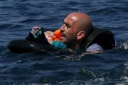A Syrian refugee holding a baby swims toward the shore after their dinghy deflated some 100 meters off the Greek island of Lesbos on Sept. 13, 2015.
