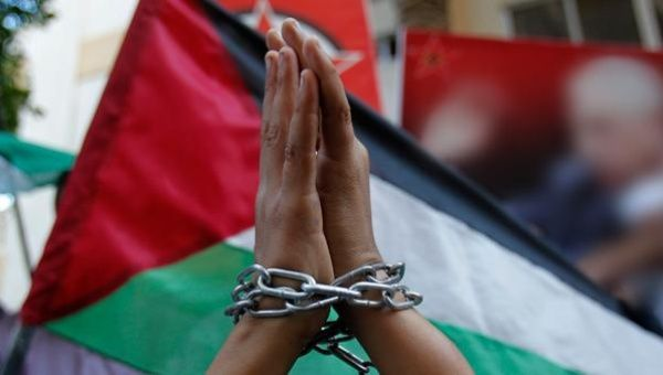 A Palestinian child raises chained hands during a protest in Gaza.