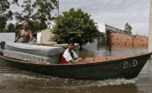 Paraguayans remove their belongings on a boat from their flooded houses near the Paraguay river in Asuncion, Dec. 27, 2015.