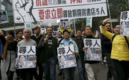 "Demonstrators hold up portraits of five missing staff members of a publishing house and a bookstore during a protest over the disappearance of booksellers, in Hong Kong, China. The banner reads, ""Against political kidnapping. Safeguarding One Country, Two Systems. Demanding the immediate release of the five people from Causeway Bay Books""."
