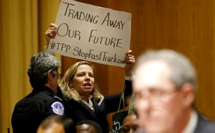 Police remove activist Margaret Flowers for protesting the Trans-Pacific Partnership during a Senate hearing in January 2015.