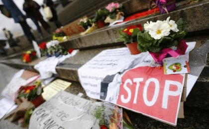Flowers and posters are placed in the square between the city cathedral and the railway station in Cologne, Germany, Jan. 11, 2016, where the vast majority of dozens of New Year Eve assaults on women took place.