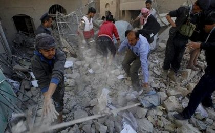 Policemen and medics remove debris as they search for victims at the site of a Saudi-led airstrike in Yemen