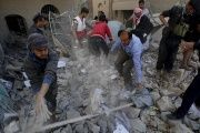 Policemen and medics remove debris as they search for victims at the site of a Saudi-led airstrike on the police headquarters in Sanaa, Jan. 18, 2016.