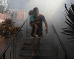 A man carries his son as health workers fumigates the Altos del Cerro neighbourhood to combat the Zika virus in Soyapango, El Salvador Jan. 21, 2016.